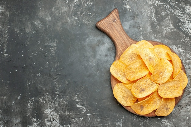 Top view of delicious homemade chips on wooden cutting board on gray background