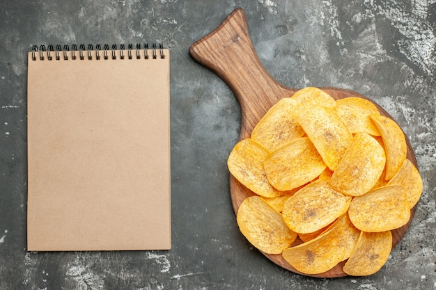 Top view of delicious homemade chips on wooden cutting board and notebook on gray background