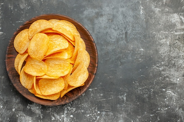 Top view of delicious homemade potato chips on a brown plate on gray background