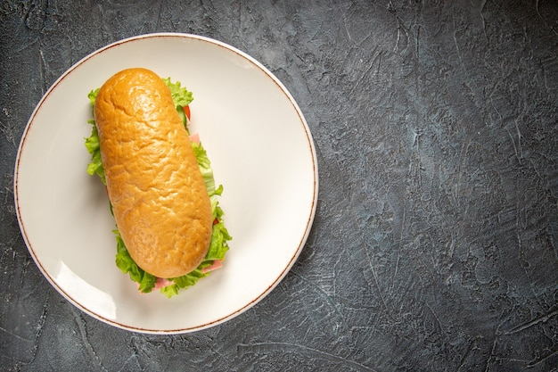 Vista dall'alto di un delizioso panino fatto in casa su un piatto bianco sul lato destro sulla superficie nera in difficoltà