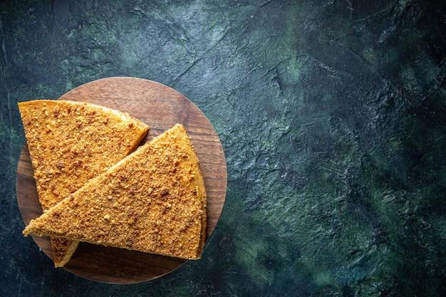 Vista dall'alto deliziosa torta al miele sulla superficie scura del bordo di legno rotondo