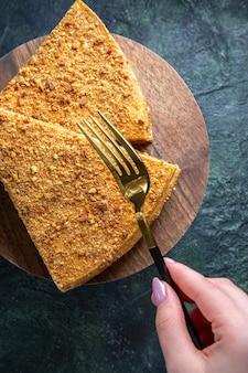 둥근 나무 보드 어두운 표면에 그것의 상위 뷰 맛있는 꿀 케이크 조각