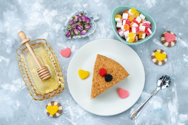 A top view delicious honey cake with candies honey on the blue background cake tea candy bake dessert