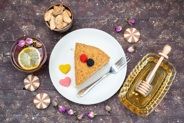 A top view delicious honey cake with candies honey and flowers on the dark background cake tea candy