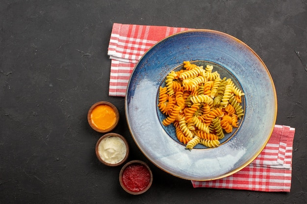 Top view delicious italian pasta unusual cooked spiral pasta on the dark background pasta dish meal cooking dinner