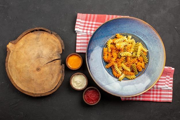 Vista dall'alto deliziosa pasta italiana insolita pasta a spirale cotta su un piatto di pasta da scrivania scuro che cucina la cena