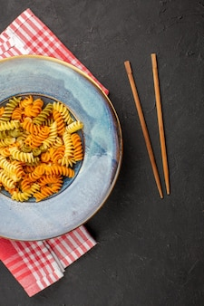 Top view delicious italian pasta unusual cooked spiral pasta inside plate on dark background pasta dish dinner meal cooking