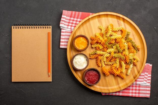 上面図おいしいイタリアンパスタ珍しい調理済みスパイラルパスタ、暗い背景に調味料を添えた料理料理パスタ