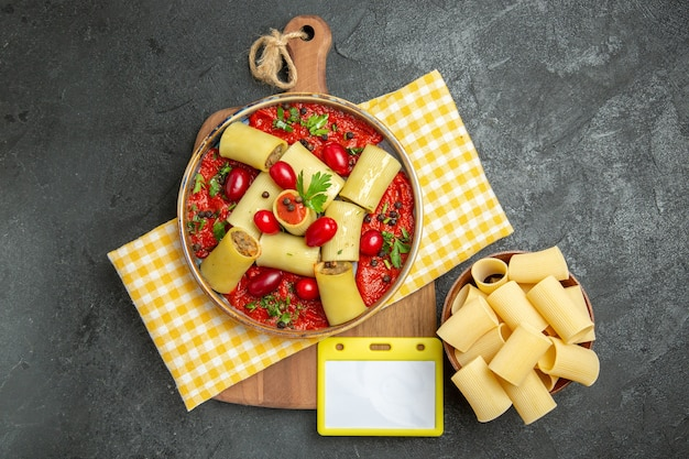 トップビューダークグレーの壁に肉とトマトソースのおいしいイタリアンパスタミールパスタフードディナー生地