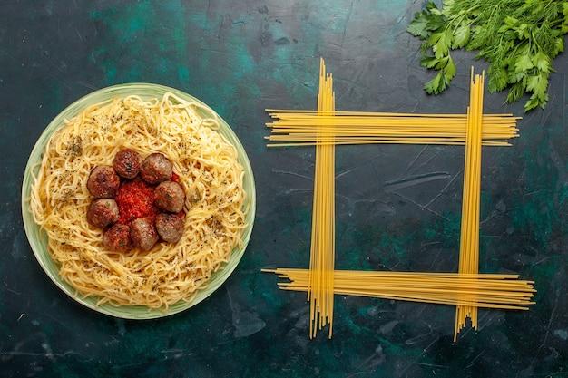 Вид сверху вкусной итальянской пасты с фрикадельками и томатным соусом на темно-синем фоне тесто макароны блюдо ужин еда италия