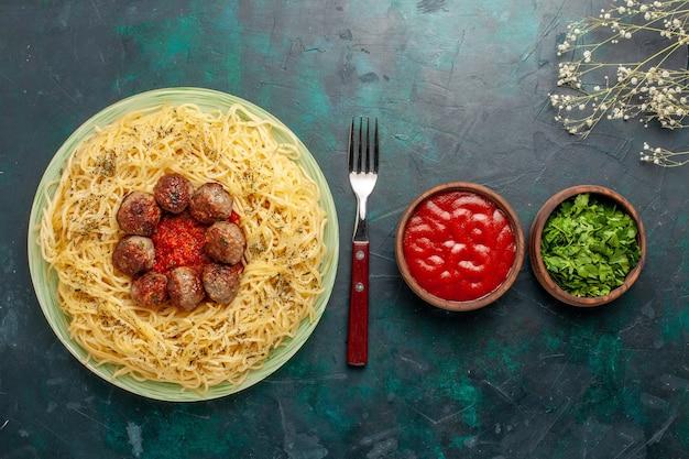 トップビューミートボールとトマトソースのおいしいイタリアンパスタ、ダークブルーのデスク生地パスタフードミールディッシュディナー
