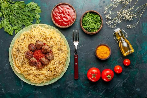 上面図青い机の上にミートボールとトマトソースが入ったおいしいイタリアンパスタ生地パスタ料理肉ディナーフードイタリア