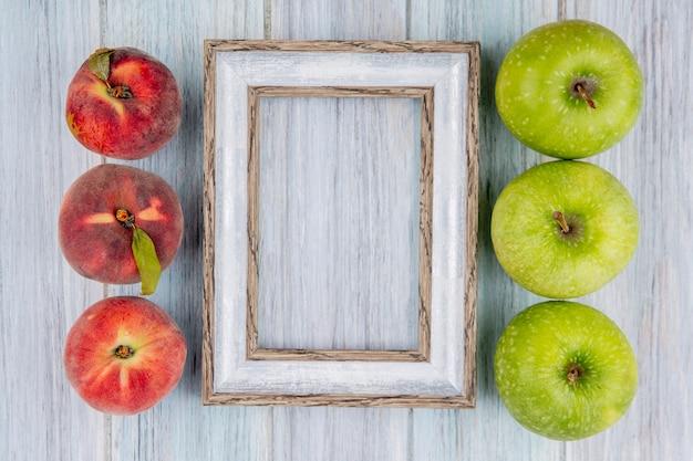 Vista dall'alto di deliziosi frutti succosi e colorati come mele e pesche su legno grigio con spazio di copia