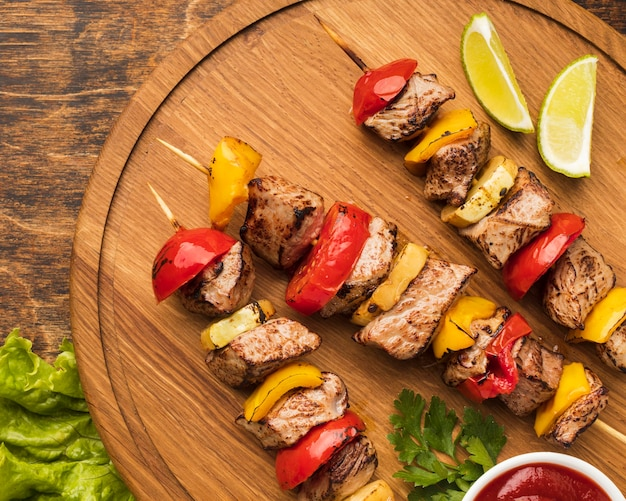 Top view of delicious kebab on chopping board with lemon