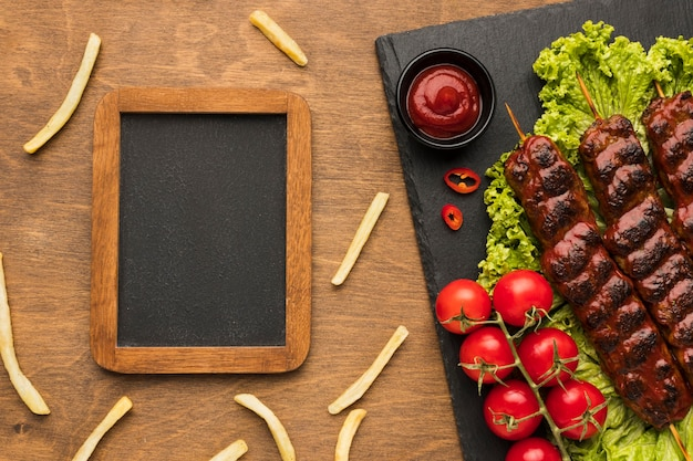 Top view of delicious kebab on slate with frame and french fries
