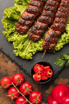 Top view of delicious kebab on slate with salad and tomatoes
