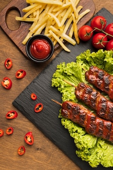 Top view of delicious kebab on slate with tomatoes and fries