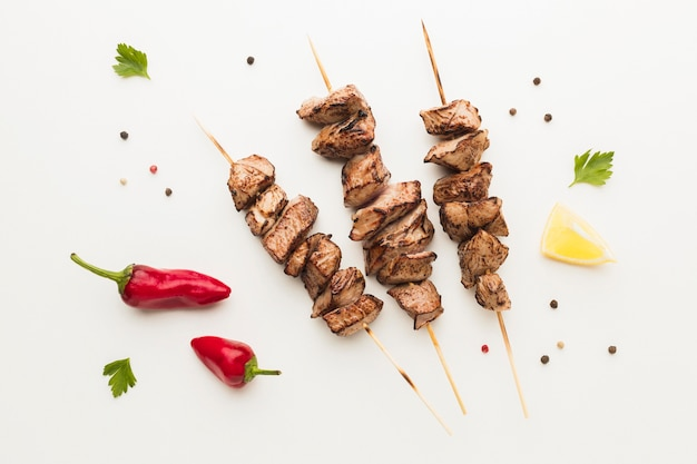 Top view of delicious kebab with chili peppers and herbs