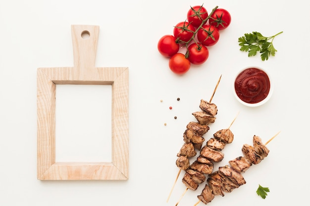 Top view of delicious kebab with frame and tomatoes