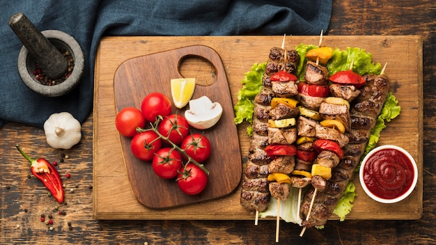 Top view of delicious kebab with meat and vegetables on chopping board