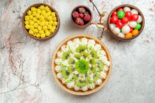 Вид сверху вкусный десерт из киви с конфетами на белом фоне десертный торт крем фруктовый тропический
