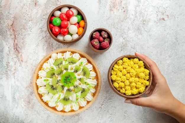 Вид сверху вкусный десерт из киви с конфетами на белом фоне десерт фруктовые конфеты кремовый торт