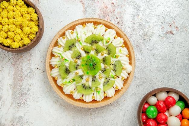 Вид сверху вкусный десерт из киви с белым кремом и конфетами на белом фоне десерт конфеты кремовый торт фрукты