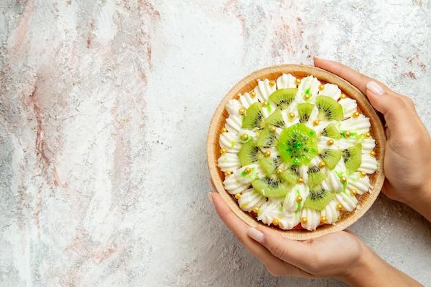 Вид сверху вкусный десерт из киви с белыми сливками и нарезанный киви на белом фоне десерт фруктовый торт кремовый торт