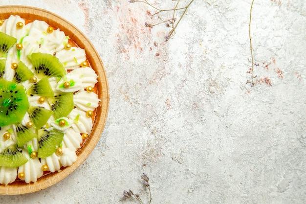 Вид сверху вкусный десерт из киви с вкусными белыми сливками и нарезанными фруктами на белом фоне десертный торт крем фруктовый тропический