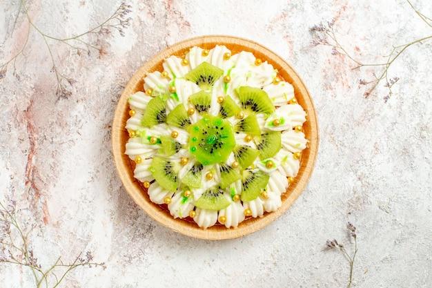 Vista dall'alto delizioso dessert al kiwi con crema bianca squisita e frutta a fette su fondo bianco torta di dessert crema di frutta tropicale