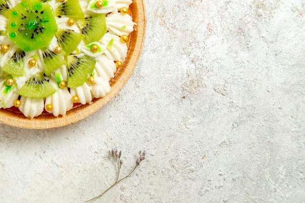 Vista dall'alto delizioso dessert al kiwi con crema bianca squisita e frutta a fette su scrivania bianca torta dessert crema frutta tropicale