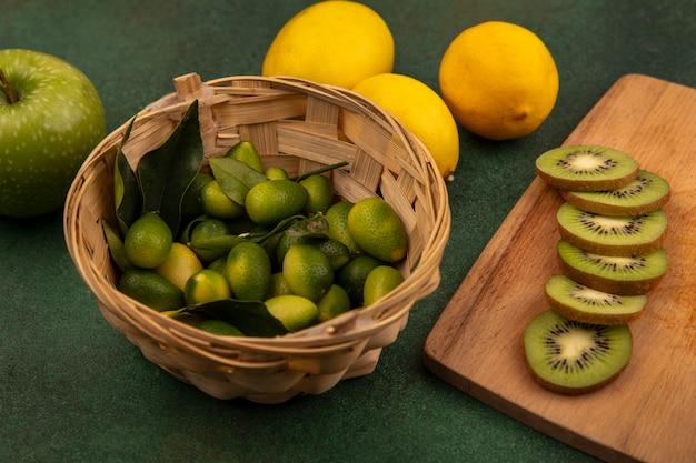 Vista dall'alto di deliziose fette di kiwi su una tavola da cucina in legno con kinkans su un secchio con limoni e mela isolata su una superficie verde