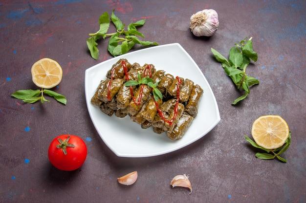 Vista dall'alto deliziosa foglia dolma piatto di carne macinata all'interno del piatto sullo sfondo scuro piatto di carne foglia cibo per la cena