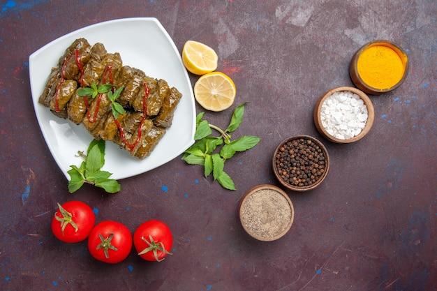 暗い背景にレモンとトマトを添えたトップビューのおいしいリーフドルマひき肉料理リーフディナーフードミート