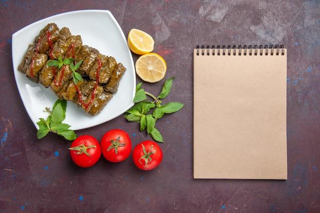 Vista dall'alto deliziosa foglia di dolma piatto di carne macinata con limone e pomodori sullo sfondo scuro piatto di foglie di cena cibo carne dinner