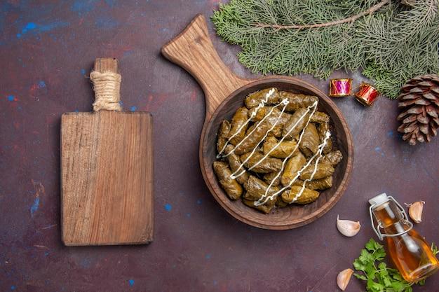 Vista dall'alto delizioso piatto di carne dolma foglia con diversi condimenti su sfondo scuro piatto di carne piatto cibo calorie