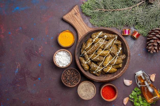 Vista dall'alto delizioso piatto di carne dolma foglia con condimenti su sfondo scuro piatto di carne piatto cibo calorie colore