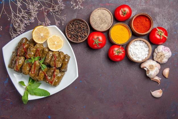 暗い背景にさまざまな調味料とトマトを使ったおいしい葉のドルマを上から見た肉料理葉料理夕食の食事