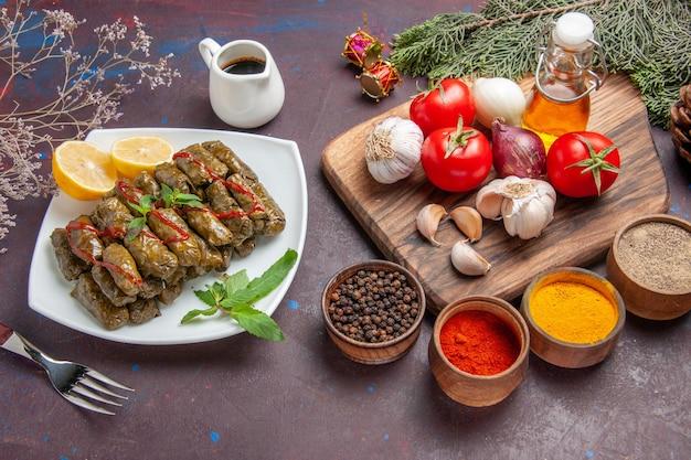 Вид сверху вкусной листовой долмы со свежими овощами и приправами на темном фоне блюдо еды листовое мясо ужин еда