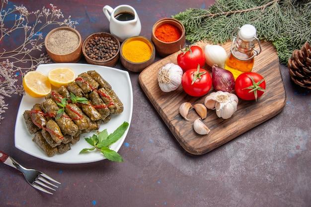 暗い背景に新鮮な野菜と調味料を添えたトップビューのおいしい葉ドルマ食事料理葉肉夕食