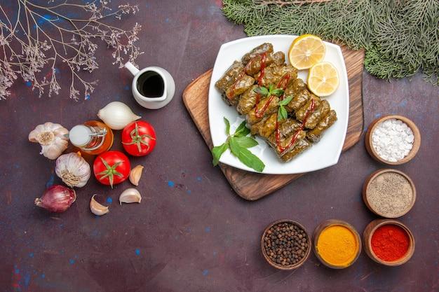 Vista dall'alto delizioso dolma a foglia con verdure fresche e condimenti su piatto da scrivania scuro piatto a base di carne a base di carne per la cena