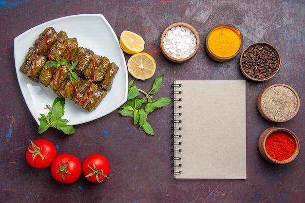 暗い背景にレモン調味料とトマトを添えたトップビューのおいしい葉のドルマ料理葉ディナー食品肉