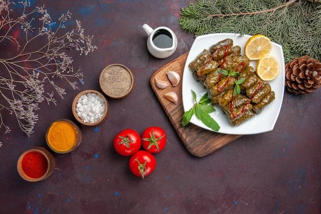 暗い背景にレモンスライスと調味料を添えたトップビューのおいしい葉のドルマ食事料理葉肉ディナーフード