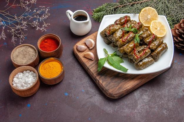Вид сверху вкусной листовой долмы с ломтиками лимона и приправами на темном фоне блюдо мясной еды листовой ужин