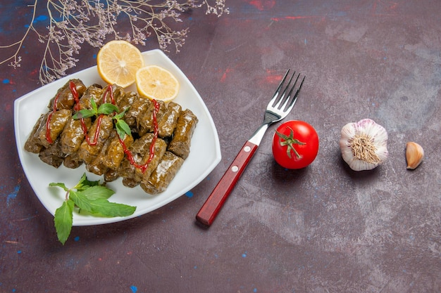 Top view delicious leaf dolma with lemon slices on the dark background meat dish leaf food dinner meal