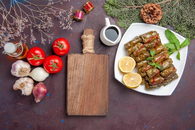 Vista dall'alto deliziosa foglia dolma con fette di limone sul pavimento scuro piatto di carne foglia cena pasto cibo