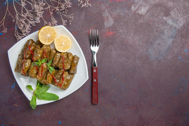 トップビュー暗い背景にレモンスライスとおいしい葉のドルマ肉料理葉の食べ物夕食の食事