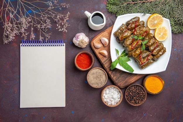 Vista dall'alto deliziosa foglia dolma con fette di limone e condimenti su scrivania scura piatto di carne foglia cena pasto cibo