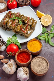暗い背景の料理に調味料とトマトを添えたトップビューのおいしい葉ドルマは、食べ物の肉の夕食を残します