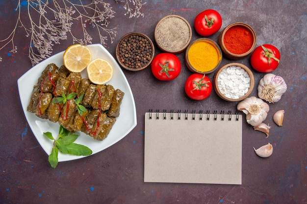 暗い背景に調味料とトマトを添えたトップビューのおいしい葉のドルマ肉料理葉の食べ物夕食の食事